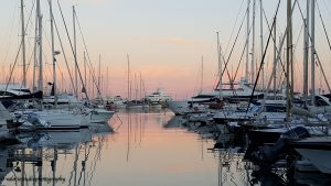 Med season blog article superyachts in a marina at sunset